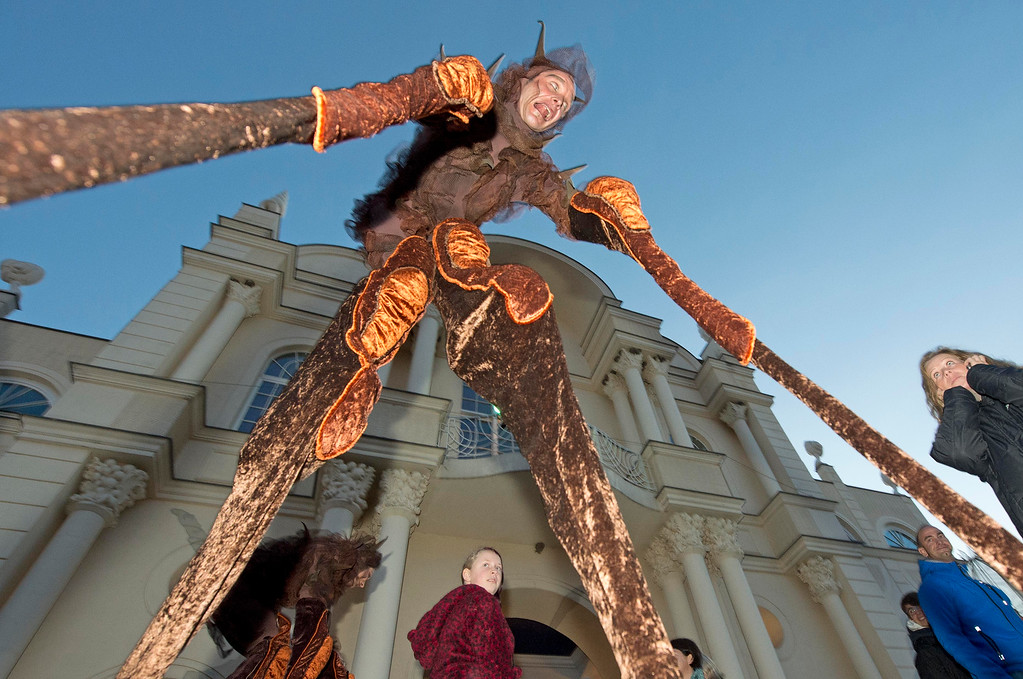 . An actor dressed as a spider walks between the visitors during a Halloween celebration in the leisure park \'BELANTIS\', the largest theme park in eastern Germany, in Leipzig, central Germany, Thursday, Oct. 31, 2013. The  park staged a Halloween party with creepy surprises for the visitors. (AP Photo/Jens Meyer)