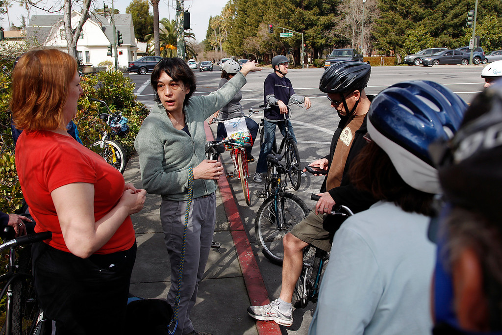 . At center left, Parks Commissioner Thida Cornes talks about the hazards to bicyclists of crossing the 6-lane Shoreline Blvd. (in background), near Villa Street  during the Great Streets Rengstorff Park Neighbor Bike Tour in Mountain View, Calif. on Sat., March 2, 2013. (LiPo Ching/Staff)