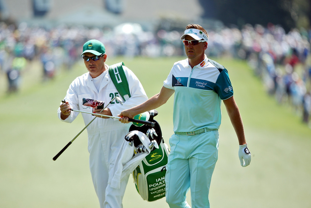 . Ian Poulter of England of England walks with his caddie Terry Mundy on the first hole during the third round of the 2014 Masters Tournament at Augusta National Golf Club on April 12, 2014 in Augusta, Georgia.  (Photo by Andrew Redington/Getty Images)