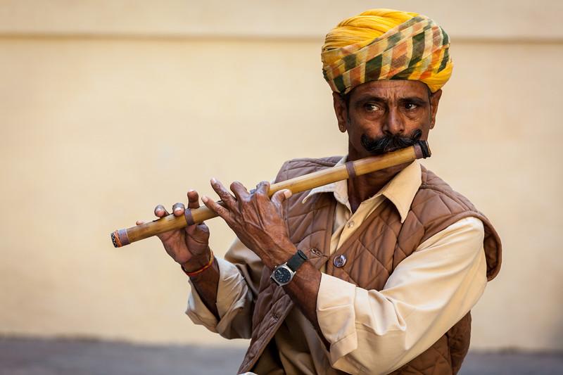 Indian man plays wooden flute in Mehrangarh fort