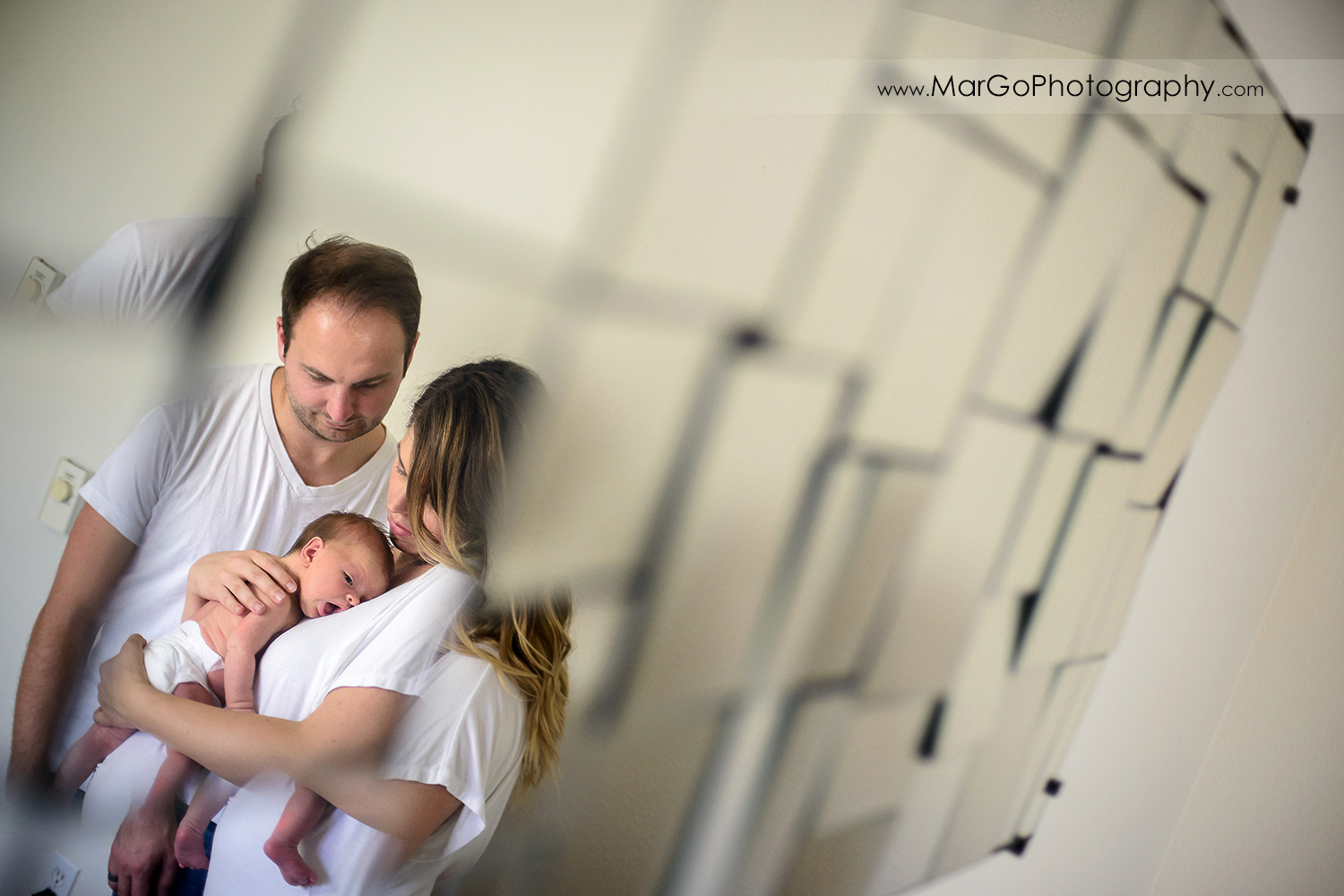 mirror shot of mother and father in white T-shirts holding newborn during family session