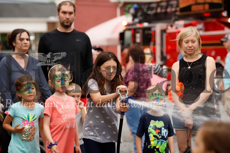 Isabelle Hildebrand, 8, and other kids took turns practicing their fireman skills Thursday at the Harmony Fire Department as part of Harmony's Fourth of July Festivities. Seb Foltz/Butler Eagle