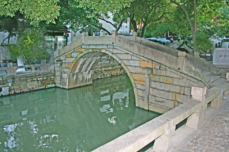 a small foot-bridge crossing a canal in Suzhou, China