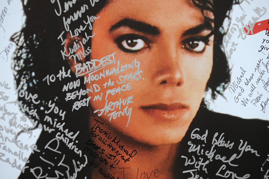 ". A poster of Michael Jackson is covered with messages from fans at a one-day tribute to the ""King of Pop\"" which included outdoor screenings of \""The Wiz\"" and \""Thriller\"" at Universal CityWalk in Universal City, California on July 9, 2009.  (ROBYN BECK/AFP/Getty Images)"