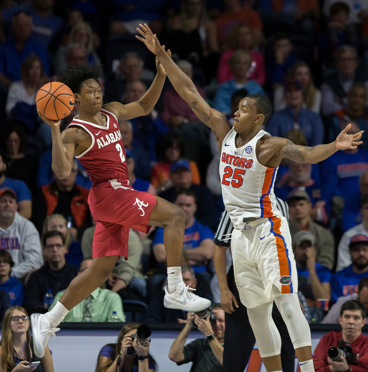 . Alabama guard Collin Sexton (2) looks to pass around Florida forward Keith Stone (25) during the second half of an NCAA college basketball game in Gainesville, Fla., Saturday, Feb. 3, 2018. (AP Photo/Ron Irby)