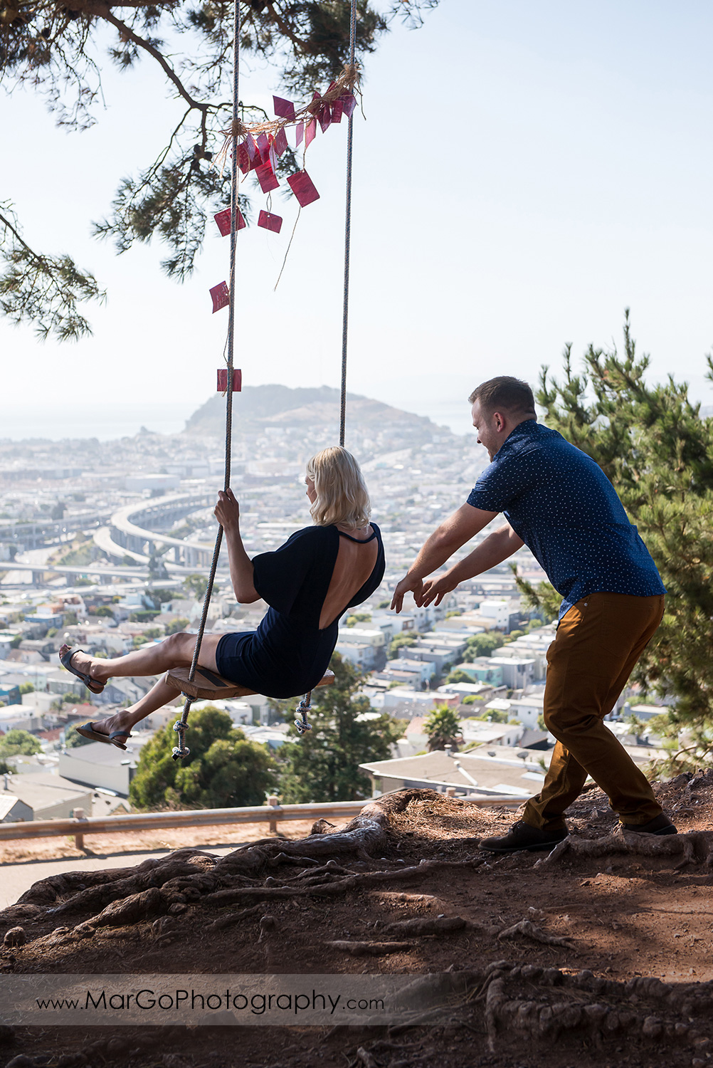 engagement session at Bernal Heights in San Francisco - couple on the swing with SF view