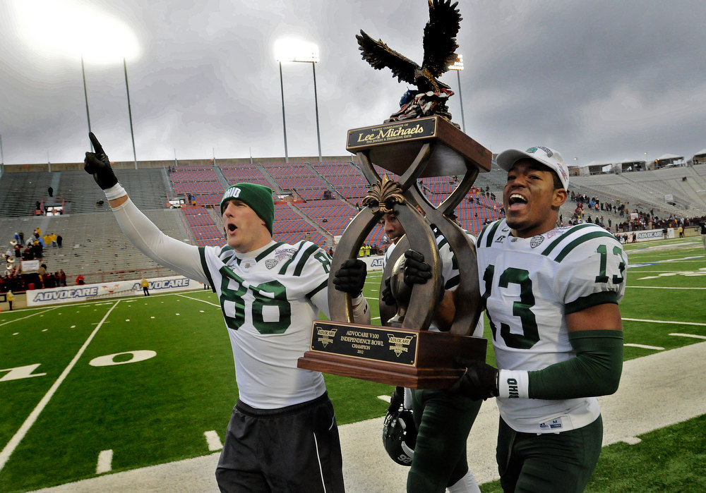 Description of . Ohio\'s Jordan Thompson (88) Gersald Moore carry the trophy down field after their 45-14 win over Louisiana-Monroe in the Independence Bowl NCAA college football game in Shreveport, La., Friday, Dec. 28, 2012.  (AP Photo/The Shreveport Times, Douglas Collier)
