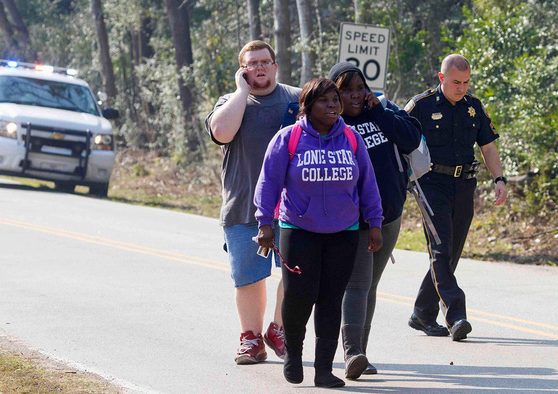 . Students evacuate on foot with a Sheriff\'s Deputy alongside at the Lone Star College North Harris campus in Houston, Texas, January 22, 2013. A shooting broke out between two people on the campus on Tuesday and there were three injuries, including one of the shooters, police and a school spokesman said. REUTERS/Richard Carson