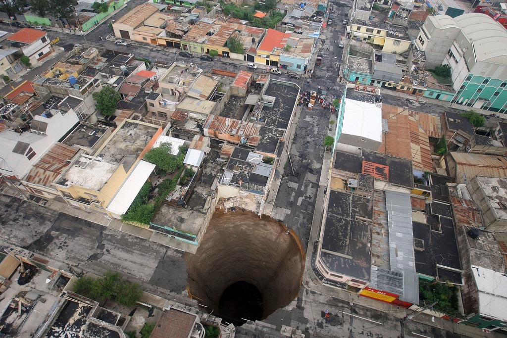 . A giant sinkhole caused by the rains of Tropical Storm Agatha is seen in Guatemala City May 31, 2010. More than 94,000 people have been evacuated as the storm buried homes under mud, swept away a highway bridge near Guatemala City and opened up sinkholes in the capital.   REUTERS/Casa Presidencial/Handout