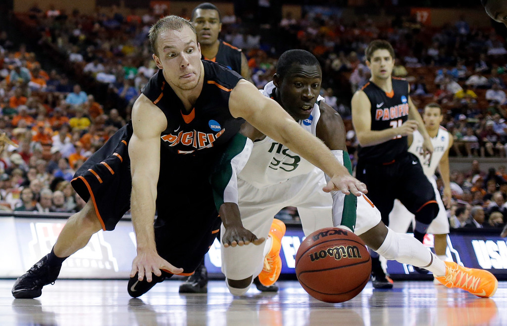 . Pacific\'s Travis Fulton and Miami\'s Tonye Jekiri (23) go after a loose ball during the second half of a second-round game of the NCAA college basketball tournament Friday, March 22, 2013, in Austin, Texas.  (AP Photo/Eric Gay)
