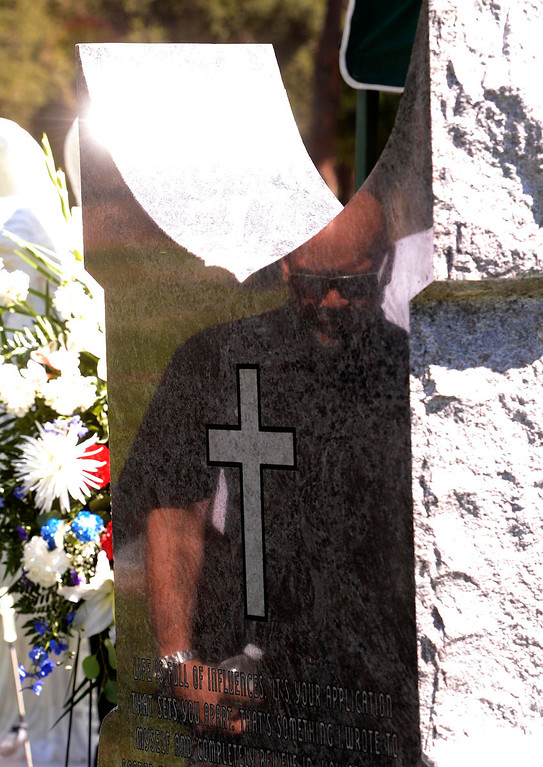 """. A visitor\'s image is reflected on the back side of a monument for Charles \""""Mask\""""  Lewis Jr. at Mountain View Cemetery in San Bernardino, CA on Saturday September 7, 2013.  (Photo by Gabriel Luis Acosta/San Bernardino Sun)"""