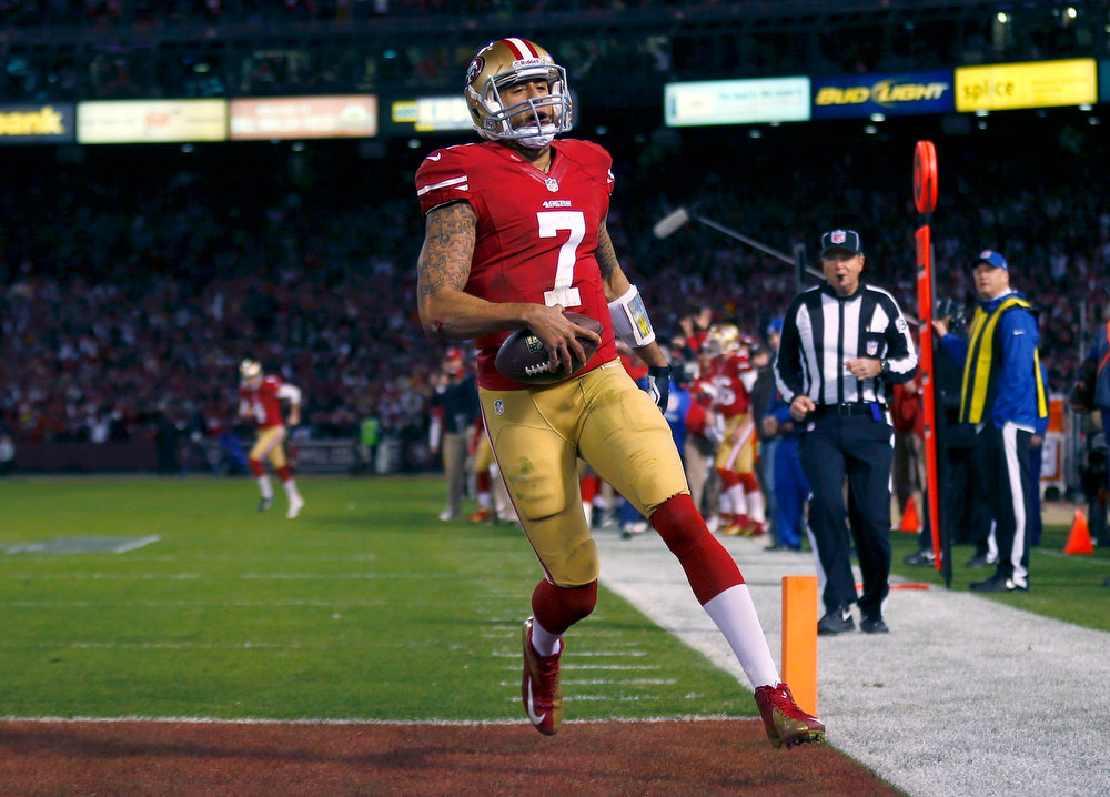 Description of . San Francisco 49ers quarterback Colin Kaepernick scores a touchdown against the Green Bay Packers in the first quarter during their NFL NFC Divisional playoff football game in San Francisco, California, January 12, 2013. REUTERS/Mike Blake