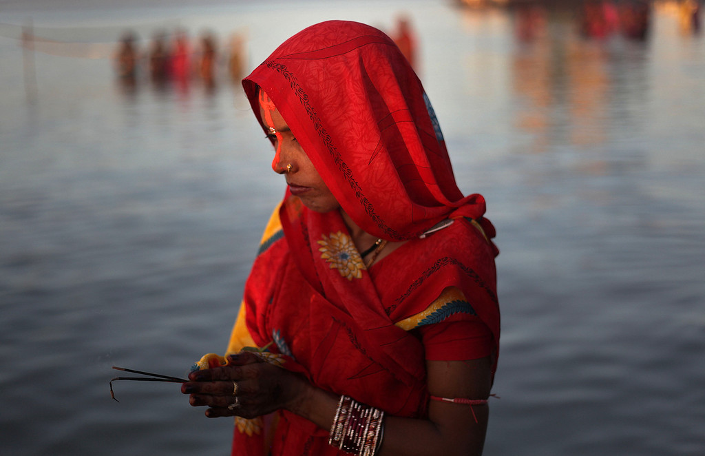. A Hindu devotee performs rituals to the setting sun in the River Brahmaputra during Chhath Puja festival in Gauhati, India, Friday, Nov. 8, 2013. .  (AP Photo/Anupam Nath)