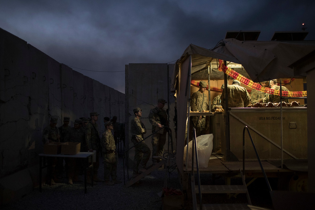 . U.S. military personnel wait in line for Thanksgiving dinner at a coalition air base in Qayara south of Mosul, Iraq, Thursday, Nov. 24, 2016. (AP Photo/Felipe Dana)