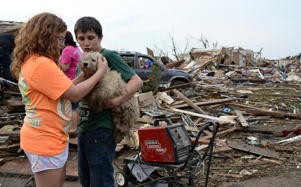 . Abby Madi (L) and Peterson Zatterlee comforts Zaterlee\'s dog Rippy, after a tornado struck Moore, Oklahoma, May 20, 2013. A 2-mile-wide (3-km-wide) tornado tore through the Oklahoma City suburb of Moore on Monday, killing at least 51 people while destroying entire tracts of homes, piling cars atop one another, and trapping two dozen school children beneath rubble. REUTERS/Gene Blevins