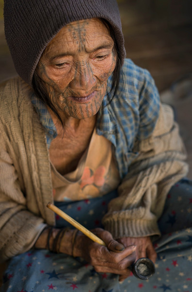 An old lady from the Muun tribe smoking the traditional pipe.  Chin State, Myanmar, 2017