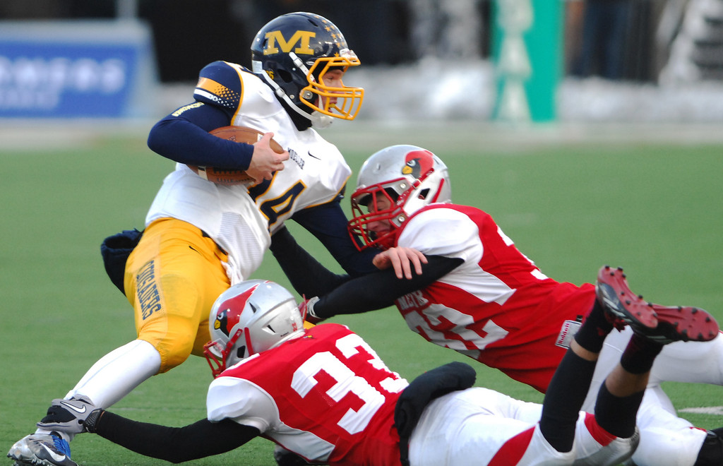 . Cincinnati Moeller quarterback Gus Ragland is tackled near the line of scrimmage by Mentor linebackers Keith McCormick (33) and JD Matsko (32) during the second quarter of Saturday\'s Div. I state championship game at Fawcett Stadium in Canton.
