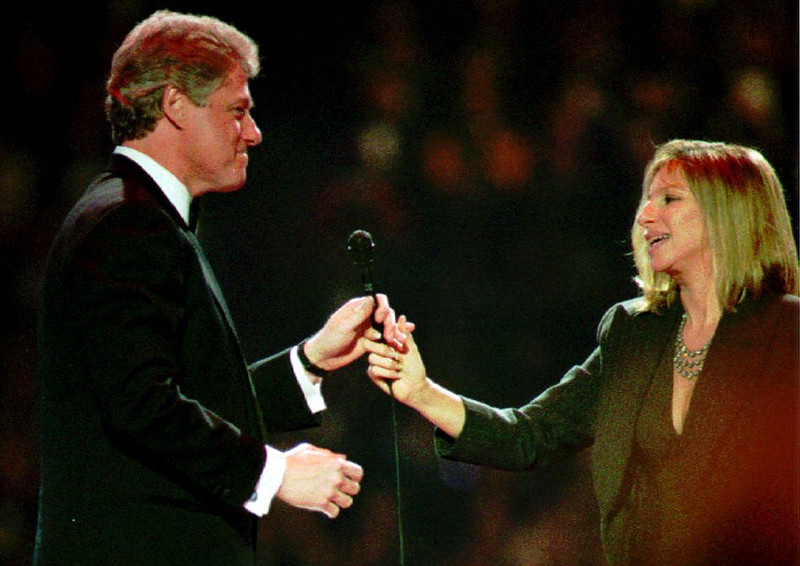 . Entertainer Barbra Streisand (R) hands the microphone to U.S. President-elect Bill Clinton as he takes the stage to address the crowd gathered for a televised inaugural gala at the Capital Centre in suburban Maryland late 19 January 1993. (POOL/AFP/Getty Images)