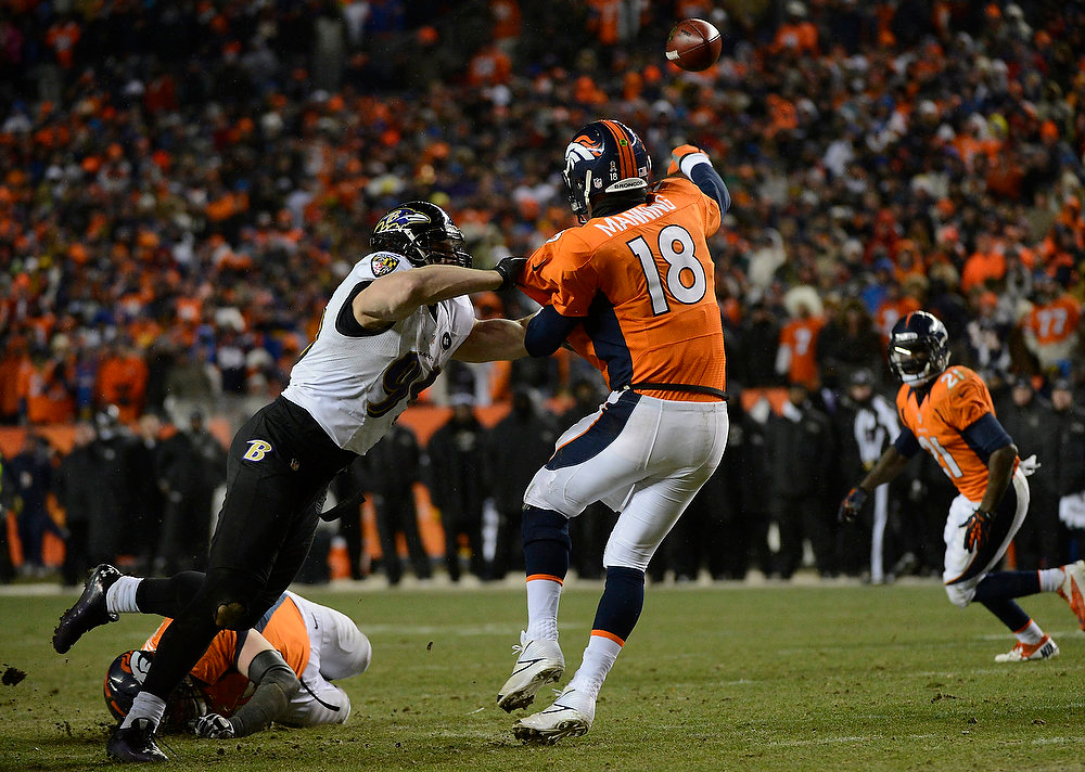 Description of . Baltimore Ravens outside linebacker Paul Kruger (99) gets to Denver Broncos quarterback Peyton Manning (18) as he throws in overtime. The Denver Broncos vs Baltimore Ravens AFC Divisional playoff game at Sports Authority Field Saturday January 12, 2013. (Photo by Joe Amon,/The Denver Post)