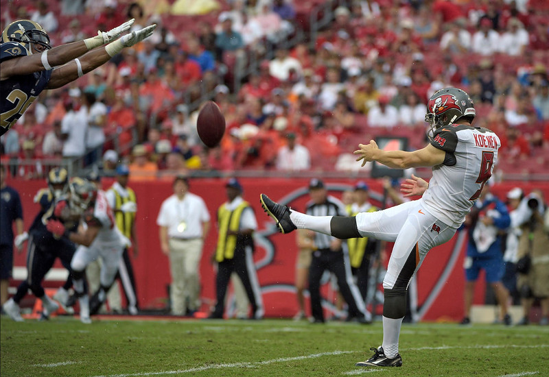 . St. Louis Rams strong safety T.J. McDonald,left, comes in to block a punt by Tampa Bay Buccaneers punter Michael Koenen (9) during the second quarter of an NFL football game Sunday, Sept. 14, 2014, in Tampa, Fla. (AP Photo/Phelan M. Ebenhack)