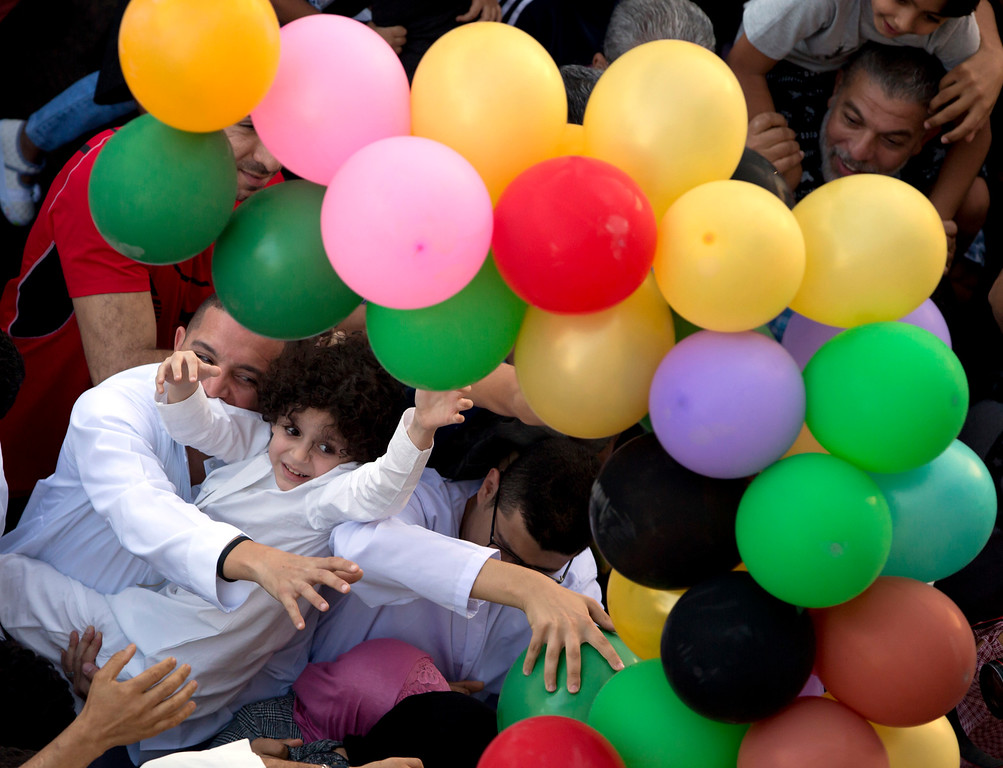 . Muslims try to catch balloons distributed for free after Eid al-Fitr prayers, marking the end of the Muslim holy fasting month of Ramadan outside al-Seddik mosque in Cairo, Egypt, Friday, June 15, 2018. (AP Photo/Amr Nabil)
