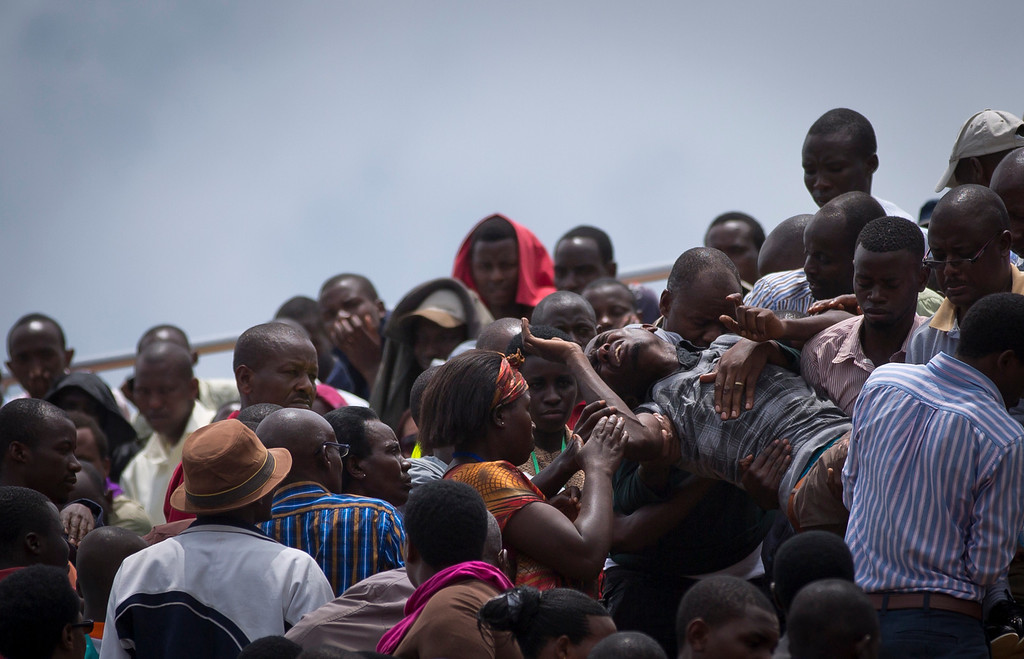 . A wailing and distraught Rwandan man, one of dozens overcome by grief at recalling the horror of the genocide, is carried away to receive help during a public ceremony to mark the 20th anniversary of the Rwandan genocide, at Amahoro stadium in Kigali, Rwanda Monday, April 7, 2014.  (AP Photo/Ben Curtis)