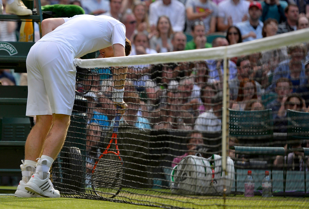 . Andy Murray of Britain leans over the net in his men\'s singles tennis match against Mikhail Youzhny of Russia at the Wimbledon Tennis Championships, in London July 1, 2013.              REUTERS/Toby Melville