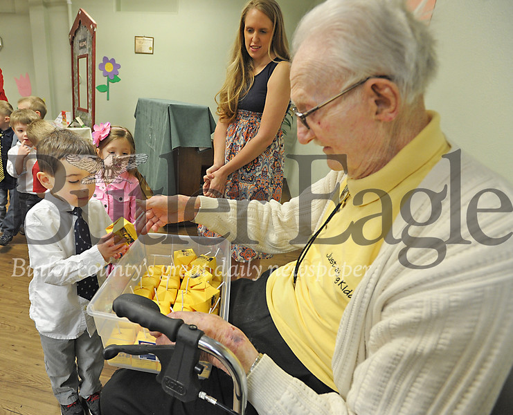 Nearly 100-year-old New Haven Court resident Harry Kidd gives out candy to Connor McGee and the rest of his honorary grandchildren at the Nixon Pre-school during a grandparents celebration on Friday, April 17, 2015.  (Tye Cypher for the Butler Eagle)