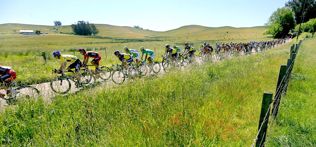 . Tejay van Garderen of team BMC, left in yellow jersey, is protected by the peloton as they roll through pastoral hills at the Sonoma, Marin County line on Highway 1 during the final stage of the Tour of California, Sunday May 19, 2013, going from San Francisco to Santa Rosa. Calif.  (AP Photo/The Press Democrat,Kent Porter )