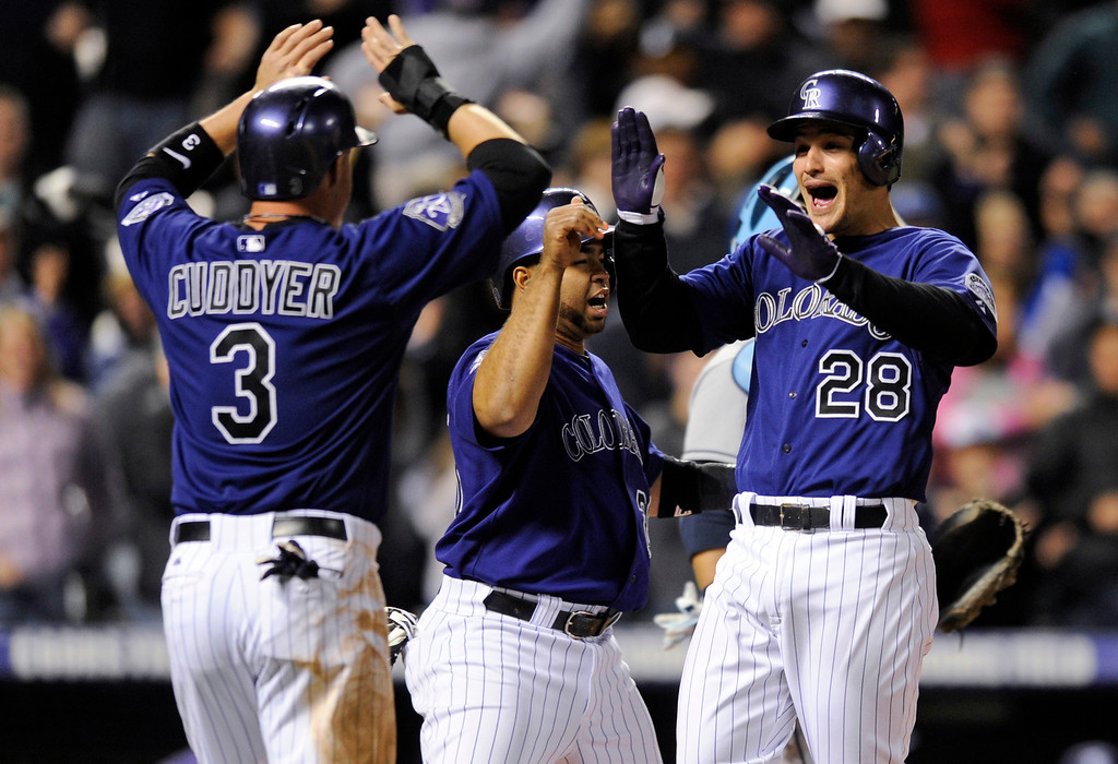 . Colorado Rockies\' Nolan Arenado (28) is congratulated by Michael Cuddyer (3) and Wilin Rosario (20) after hitting a grand slam off Tampa Bay Rays starting pitcher David Price during the seventh inning of a baseball game Saturday, May 4, 2013, in Denver. (AP Photo/Jack Dempsey)