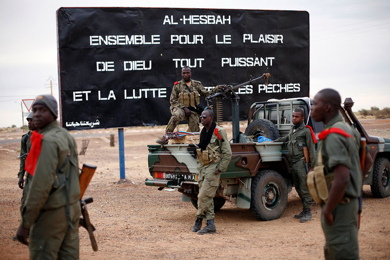 ". Malian soldiers are stationed at the entrance of of Gao, Northern Mali, Monday Jan. 28, 2013. French and Malian troops held a strategic bridge and the airport in the northern town of Gao on Sunday as their force also pressed toward Timbuktu, another stronghold of Islamic extremists in northern Mali, officials said. The sign , a reminder of Islamic extremists, reads "" Al Hesbah, together for the pleasure of God almighty and the struggle against sins.\""(AP Photo/Jerome Delay)"