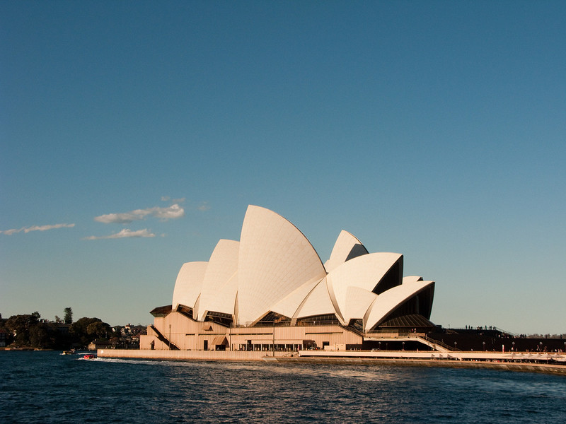The Sydney Opera House as seen from a ferry as sunset is approaching.