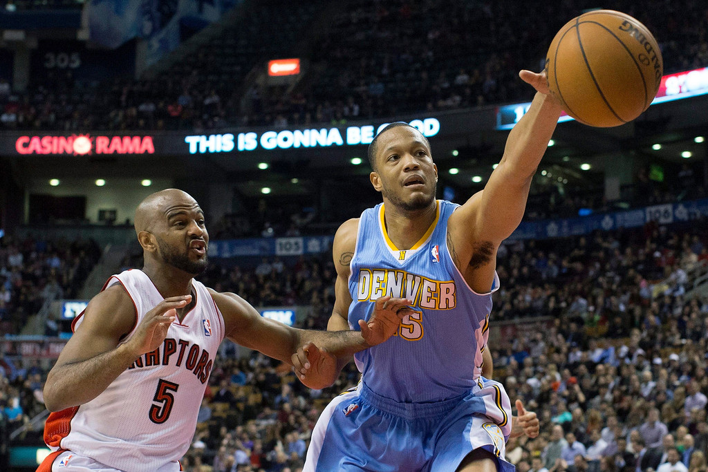 . Denver Nuggets\' Anthony Randolph reaches for the ball next to Toronto Raptors\' John Lucas during the second half of an NBA basketball game in Toronto on Tuesday, Feb. 12, 2013. (AP Photo/The Canadian Press, Chris Young)