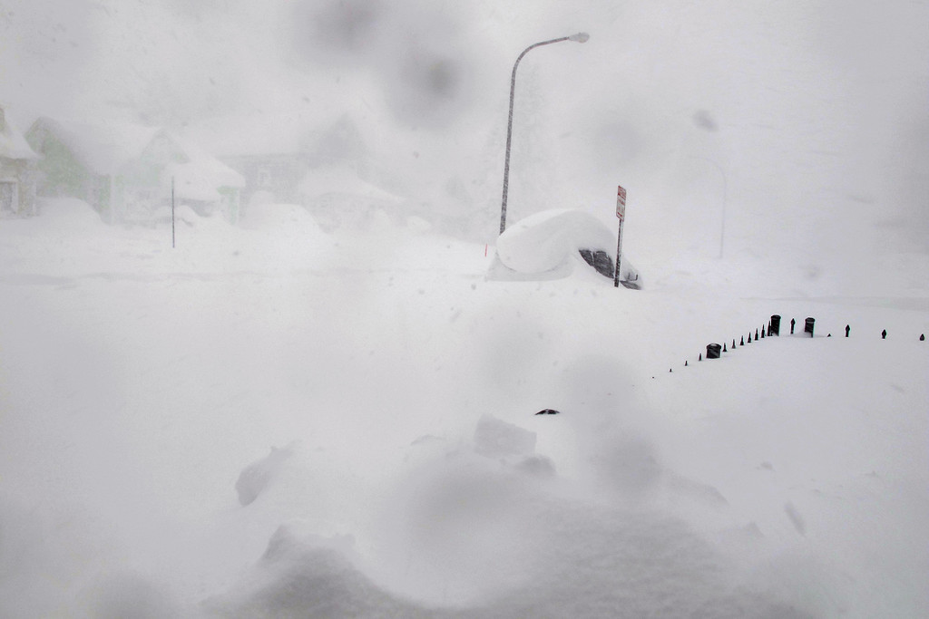 . A 4-foot fence and SUV are nearly buried along a street in Buffalo, N.Y. on Tuesday, Nov. 18, 2014.  Parts of New York measured the season\'s first big snowfall in feet, rather than inches,  as 3 feet of lake-effect snow blanketed the Buffalo area.  The Thruway Authority said white-out conditions caused by wind gusts of more than 30 mph forced the closure of Interstate 90 in both directions from the Rochester area to Ripley, on the Pennsylvania border 60 miles southwest of Buffalo.  (AP Photo/Carolyn Thompson)