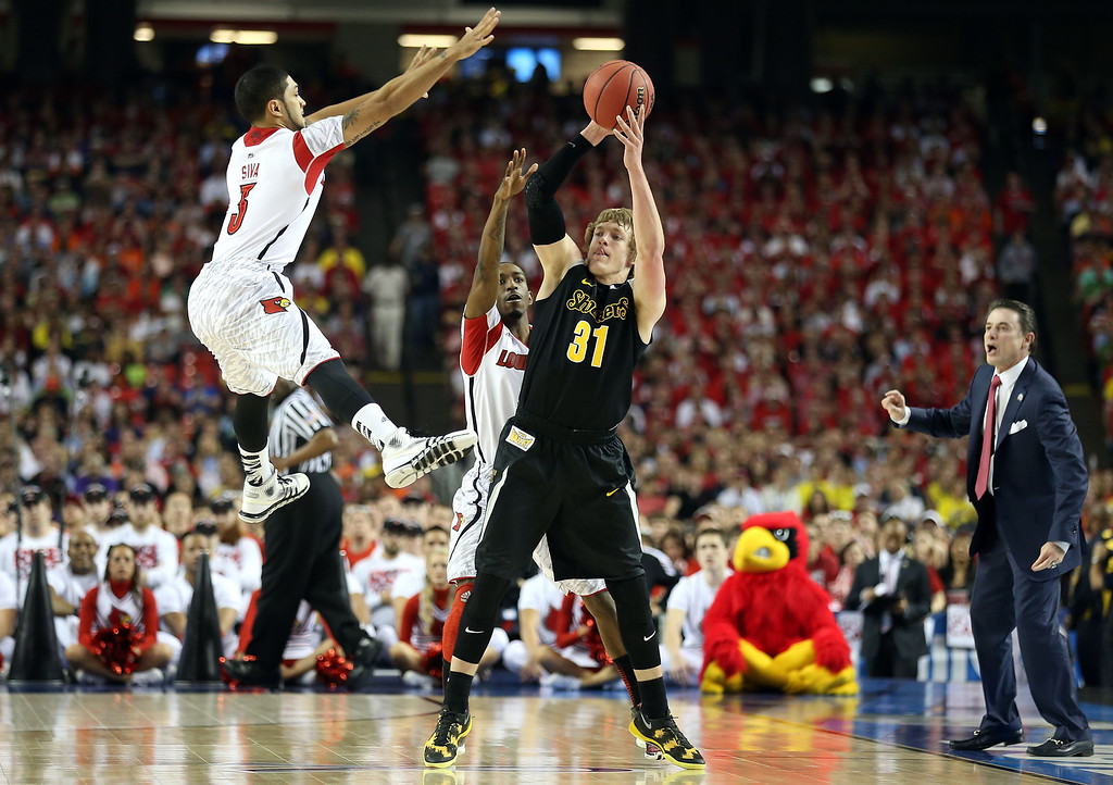 . ATLANTA, GA - APRIL 06:  Ron Baker #31 of the Wichita State Shockers looks to pass as he is pressured by Peyton Siva #3 and Russ Smith #2 of the Louisville Cardinals during the 2013 NCAA Men\'s Final Four Semifinal at the Georgia Dome on April 6, 2013 in Atlanta, Georgia.  (Photo by Andy Lyons/Getty Images)
