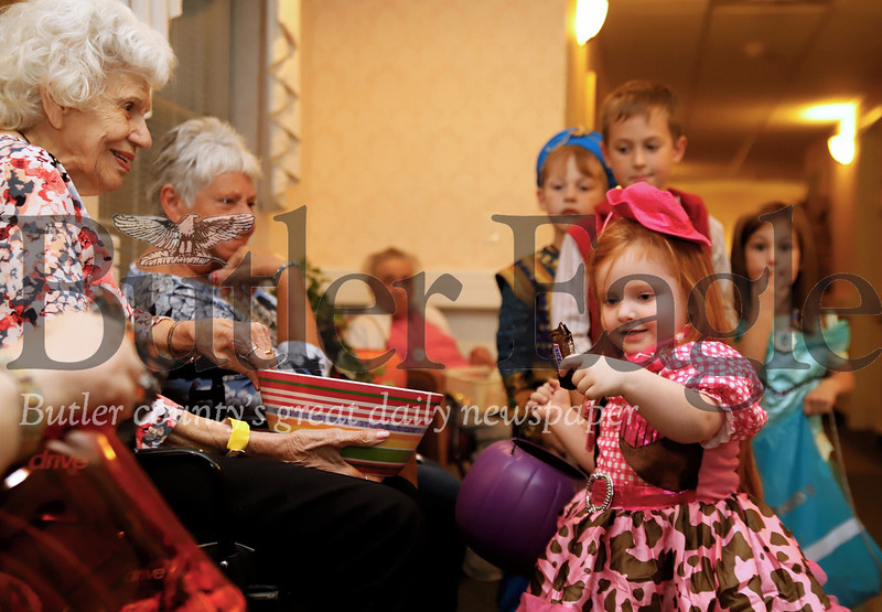 Emma Stewart, 4, picks out a Snickers from Pauline Parr's bowl  treak-or-treating at the New Haven Court at Clearview retirement home Tuesday. Costume-clad kids crowded the halls  and made their rounds in the senior community trick-or-treating with residents a of the home. Seb Foltz/Butler Eagle