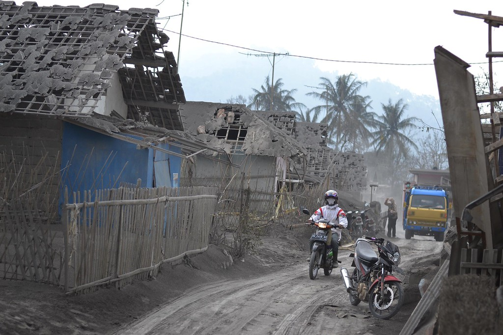 . Residents return to a village damaged by heavy ashfall in Malang, East Java on February 16, 2014 following the volcanic eruption of Mount Kelud in East Java on February 13. AFP PHOTO / Aman  ROCHMAN/AFP/Getty Images