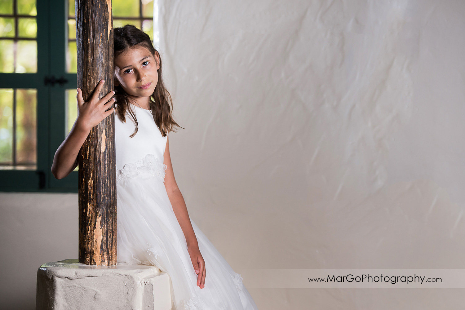 portrait of first communion girl in white dress resting on wooden pole at Cafe Wisteria in Menlo Park