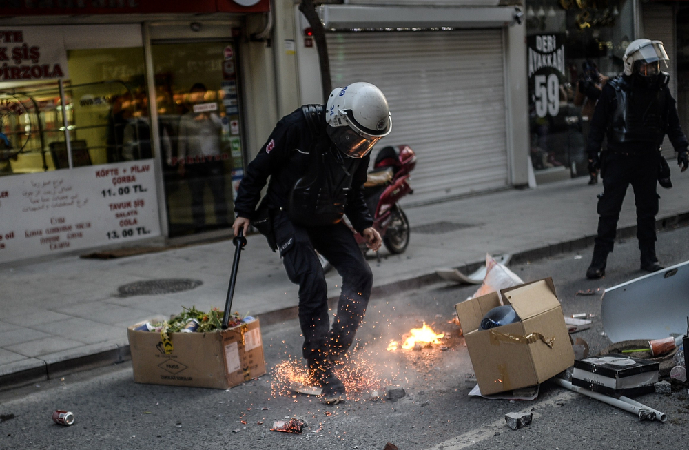 . A police officer tries to extinguish  fires  after the funeral of Berkin Elvan, the 15-year-old boy who died from injuries suffered during last year\'s anti-government protests, in Istanbul on March 12, 2014. Riot police fired tear gas and water cannon at protestors in the capital Ankara, while in Istanbul, crowds shouting anti-government slogans lit a huge fire as they made their way to a cemetery for the burial of Berkin Elvan. (BULENT KILIC/AFP/Getty Images)