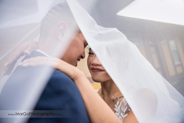 veil shot of bride an groom at train station near Sunol's Casa Bella