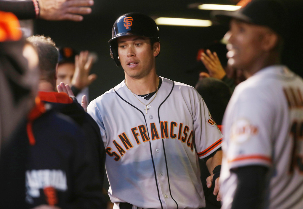 . San Francisco Giants\' Tyler Colvin is congratulated by teammates after scoring on a triple by Gregor Blanco against the Colorado Rockies in the fifth inning of a baseball game in Denver on Tuesday, May 20, 2014. (AP Photo/David Zalubowski)