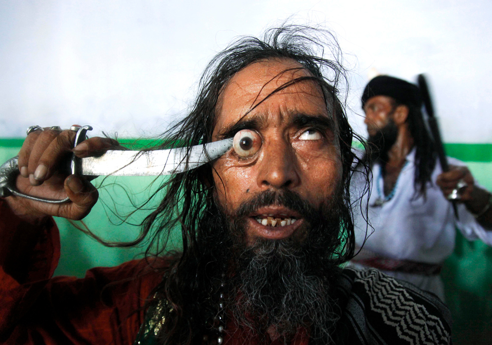 Description of . A Sufi Kalandar (or wandering ascetic) performs an act of self torture during the annual Urs festival at the shrine of Sufi saint Moinuddin Chishti in Ajmer, India, Thursday, June 9, 2011. The Urs is observed to mark the death anniversary of the saint, known for his philosophy on religious tolerance. (AP Photo/Rajesh Kumar Singh)