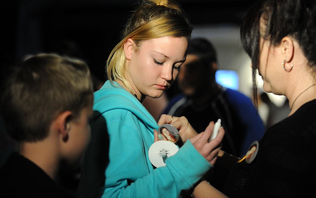 . Brianna Berg, 14, center, has a button pinned on her by her mother, Dawn, during a candlelight vigil for missing student, Sahray Barber, 22, is held on Friday, March 13, 2015 at the Art Institute of California Inland Empire in San Bernardino, Ca. The Berg family have been friends of Barber for years. (Photo by Micah Escamilla/The Sun)