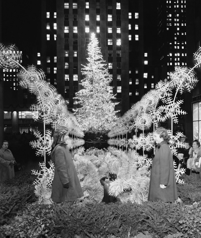 . A silver-sprayed 75-foot high Norway spruce sparkles after its 7,500 bulbs were lighted for the first time in Rockefeller Center, Dec. 9, 1949 in New York. At the same time, flood lights from buildings in the center were beamed onto the promenade where 48-spray-like metal plumes, erected in the promenade, held pin-wheels designed as snow flakes. The signal for the lighting was given by Peggy, left, and Eileen Murphy, daughters of a Rockefeller center employee. This view is made, looking west from Fifth Avenue, down the promenade toward the plaza.  (AP Photo/Tom Fitzsimmons)