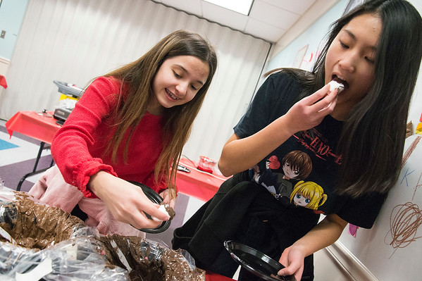 02/14/20 Wesley Bunnell | StaffrrThe Plainville Public Library held candy making during the afternoon in different sessions for K through teenagers. Janessa Freitas, age 15, and friend Christine Dai, age 14, cover marshmallows in melted chocolate.