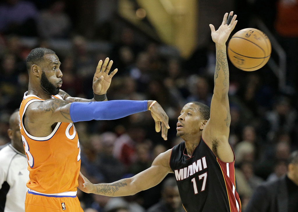. Cleveland Cavaliers\' LeBron James, left, passes around Miami Heat\'s Rodney McGruder in the second half of an NBA basketball game Friday, Dec. 9, 2016, in Cleveland. The Cavaliers won 114-84. (AP Photo/Tony Dejak)