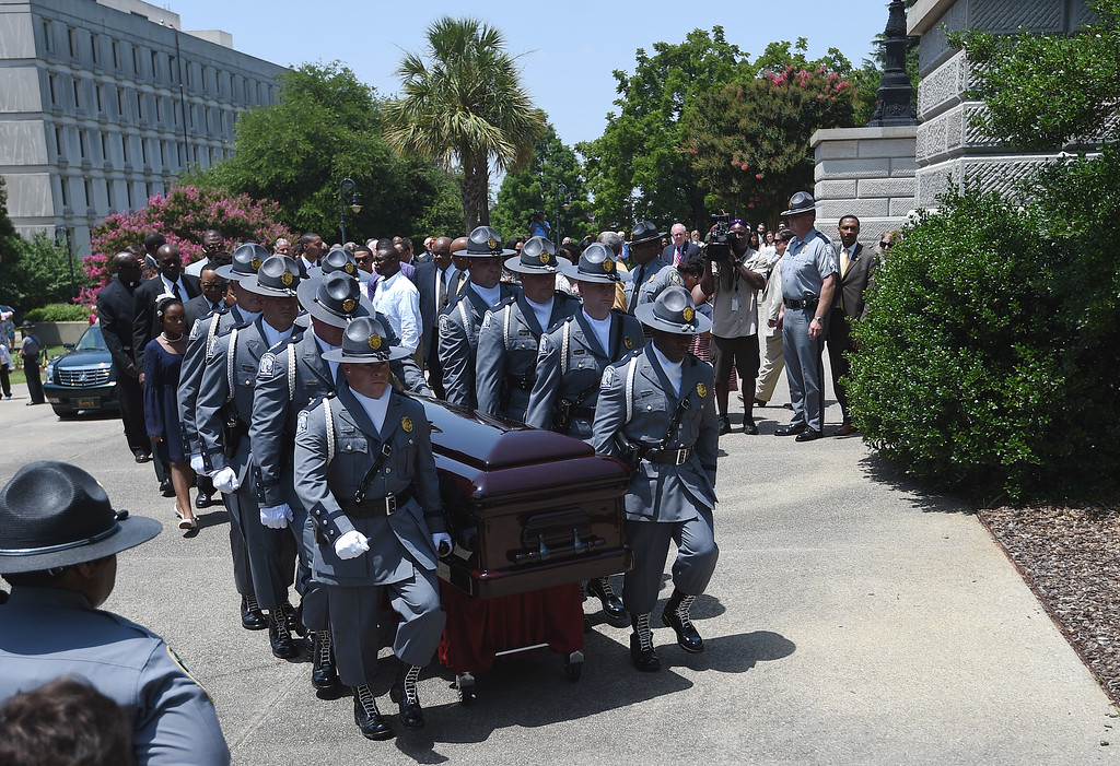 . A South Carolina Highway Patrol honor guard carries Sen. Clementa Pinckney\'s casket to the Statehouse, Wednesday, June 24, 2015, in Columbia, S.C. Pinckney\'s open coffin was being put on display under the dome where he served the state for nearly 20 years. He was one of those killed in a mass shooting at the Emanuel AME Church in Charleston.(AP Photo/Rainier Ehrhardt)