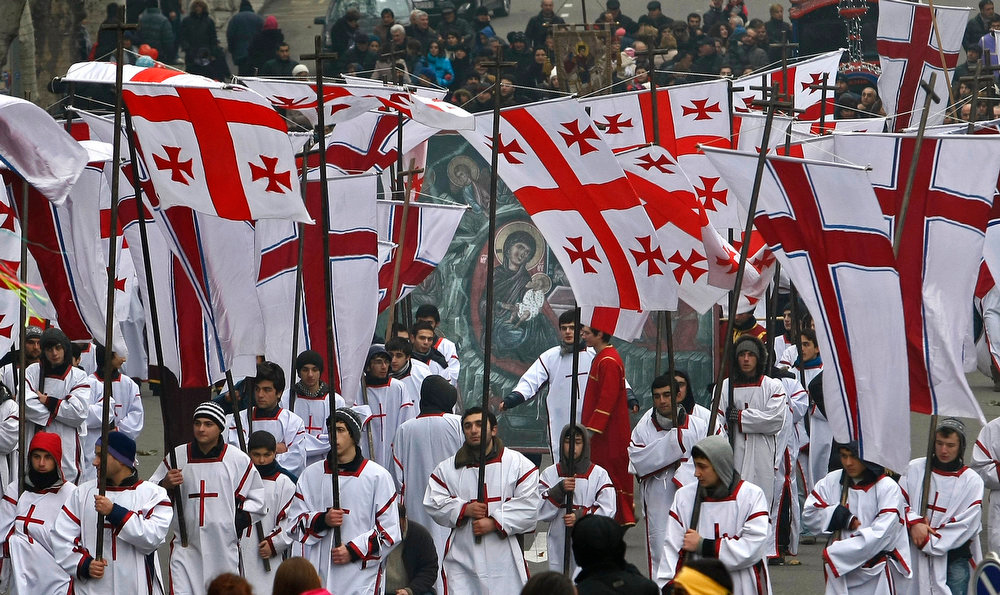 . Georgians with National flags take part in a religious procession to mark the Orthodox Christmas, in Tbilisi, Georgia, Monday,  Jan. 7, 2013. Christmas falls on Jan. 7 for Orthodox Christians that use the old Julian calendar instead of the 16th-century Gregorian calendar adopted by Catholics and Protestants and commonly used in secular life around the world. (AP Photo/Shakh Aivazov)