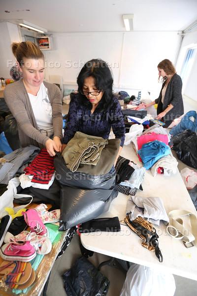 inzamelen kleding vluchtelingen wijkcentrum De Groene Loper - Vrijwilligers sorteren de kleding - LEIDSCHENDAM 25 OKTOBER 2015 - FOTO NICO SCHOUTEN
