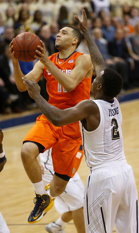 . Syracuse\'s Tyler Ennis (11) shoots past Pittsburgh\'s Michael Young (2) during the second half of an NCAA college basketball game on Wednesday, Feb. 12, 2014, in Pittsburgh. (AP Photo/Keith Srakocic)